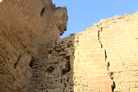 Cracks in the yellow eroded walls of the abandoned Montearagon castle in the Aragon region, Spain, against a deep blue sky during a summer day