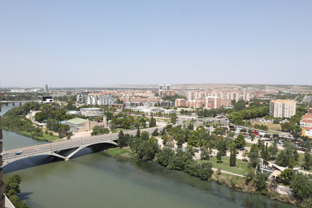 A landscape of Zaragoza city, with Ebro river shores, the Santiago bridge and the Actur district, a seen from the Pilar Catedral bell tower, Spain Imagens