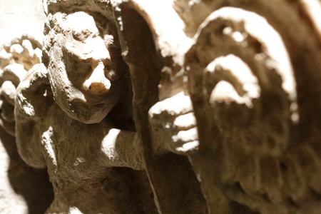 A close view of an archer shooting an arrow, carved as a low relief in the stone with a chiaroscuro effect in the Alma Mater Museum, Zaragoza, Spain Stock Photo