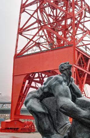 Hombre Tuercebarras (hombre de flexión de barras) escultura delante de la grua roja Carola (grúa Carola) en Bilbao, País Vasco, España, durante un día lluvioso