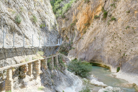 The Vero river canyon during a summer day with the hanging elevated path over it, the typical red iron rock and some trees, in Alquezar, Spain Imagens