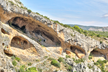 A landscape of the Vero river canyon, with mountains, eroded caverns and steep cliffs, during a sunny summer day in the rural town of Alquezar, Spain