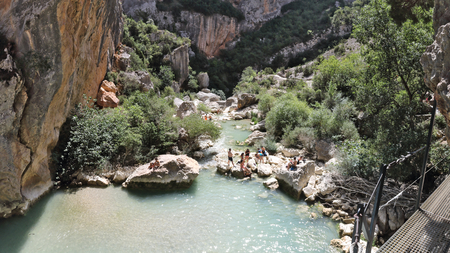People having bath in a small pond of the Vero river among rocks and cliffs of the Vero canyon and mountains in Alquezar, Spain