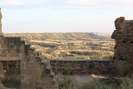 The tilled crop fields of Aragon region seen from a ruined stone defense walls of the abandoned Montearagon castle, during sunset, in Spain 写真素材