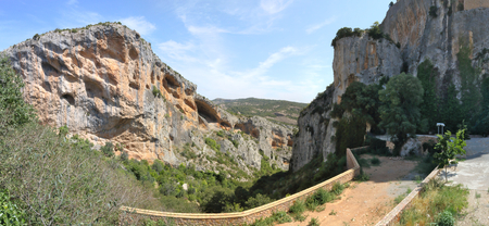 A landscape of the Vero river canyon, with pine trees mountains and steep cliffs, during a sunny summer day in the rural town of Alquezar, Spain Imagens