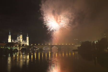 The fireworks during the 2018 Pilar festival next to the Pilar Cathedral and the Stone Bridge over the Ebro river, in Zaragoza, Aragon region, Spain