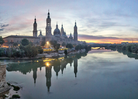 A landscape of Pilar Cathedral and Santiago Bridge reflecting in the Ebro river at sunset, after a storm, in a cloudy autumn, in Zaragoza, Spain Banque d'images
