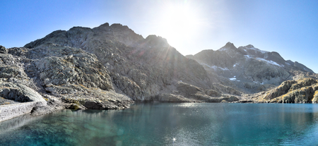 La parte inferior del Lago Azul (Ibon Azul), entre áridas montañas rocosas con nieve y un cielo azul en un otoño soleado, en Panticosa, Pirineo Aragonés, España