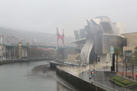 Bilbao, Spain - December 08, 2017: The Guggenheim Museum and the La Salve Bridge next to the Ria del Nervion river in Bilbao, Basque Country, Spain, during a rainy and cloudy winter day Editorial