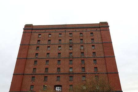 An abandoned old big industrial building made of red bricks with many periodically distributed windows in a cloudy day in Butterfly Junction, Bristol 写真素材 - 117318877
