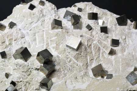 Iron pyrite cubes inside a white rock with the typical perfect geometrical shape