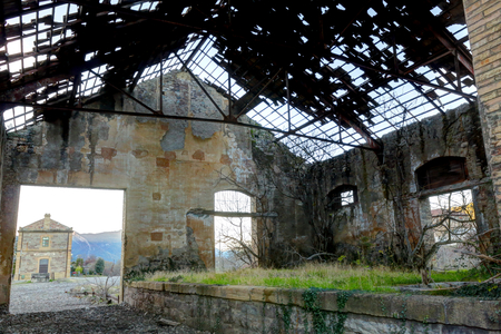 Abandoned train warehouse, with missing tiles from the roof, grass and ruined walls next to the railway in Santa Maria y La Pena train station, Spain Editorial