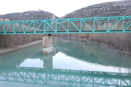 The light green metal railway bridge over the Gallego river for the train from Jaca to Zaragoza in the pre-pyrenees mountains in Aragon, Spain Stock Photo