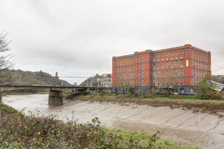 The Avon river with mud after a storm, next to a red brick abandoned industrial building and a bridge in a cloudy winter in Bristol, United Kingdom 報道画像