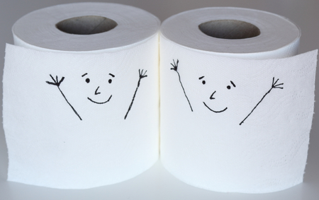 Two white toilet paper rolls sketched with two cheerful faces close to each others, representing the happiness feelings