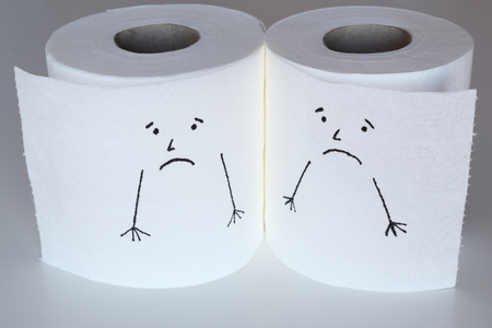 Two white toilet paper rolls sketched with sad faces close to each other, with a melancholic face, representing the sadness feelings Stock Photo