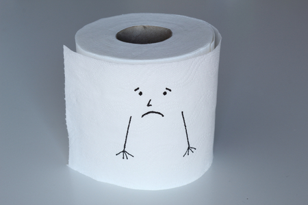 A white toilet paper roll sketched with a sad character with melancholic face and arms down, representing the sadness feeling through his face 写真素材