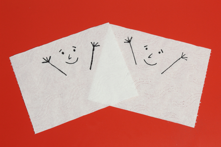 Two white toilet paper pieces sketched with two cheerful faces close to each others, representing the happiness feelings