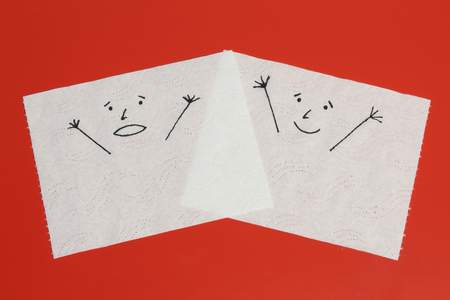 Two white toilet paper pieces sketched with a shouting and a cheerful face close to each other, representing the panic and the happiness feelings Imagens