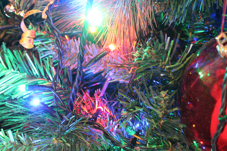 A close view of a green leaves Christmas tree with electric lights decorations and hanging ornaments in a bright colored atmosphere Фото со стока