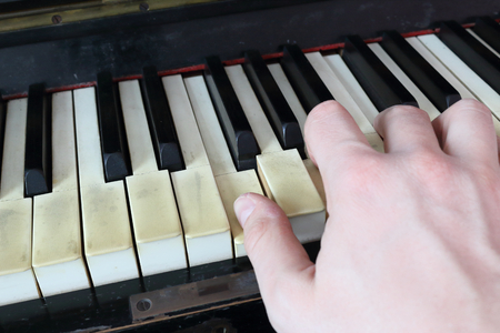 A right hand playing a F (FA) major chord on an old black piano with yellowed cracked keys, pressing the F (FA), A (LA), C (DO) notes