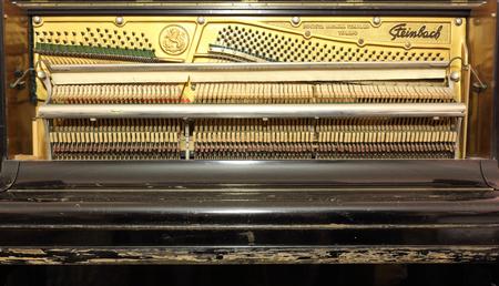Mécanique complète d'un vieux piano droit Steinbach, montrant la plaque avec les goupilles d'attelage, les cordes, les marteaux et les leviers, et le couvercle du clavier fermé