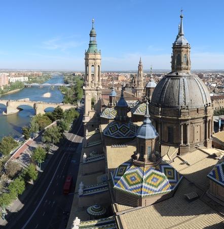 A landscape of Zaragoza with the Puente de Piedra and Puente de Hierro bridges, the Ebro river and a Pilar Cathedral bell tower, in Aragon, Spain Reklamní fotografie