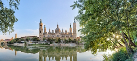 A landscape of christian Pilar Cathedral and Santiago Bridge reflecting in the Ebro river during a sunny summer day in Zaragoza, Aragon region, Spain