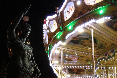 The Cesar August statue in front of carousel in an amusement park, bi night, in Zaragoza, Spain