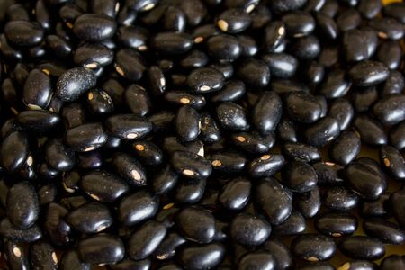 Typical and traditional black beans on top of a yellow table serving as background