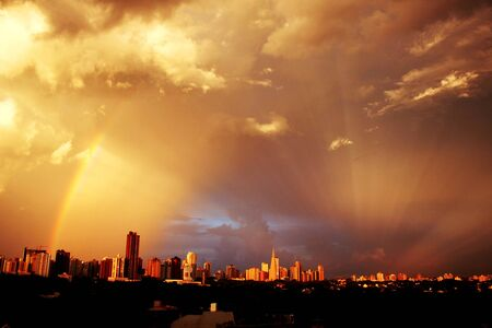 Sunset with a rainbow over the buldings and the Cathedral of Maringa, Parana, Brazil 写真素材