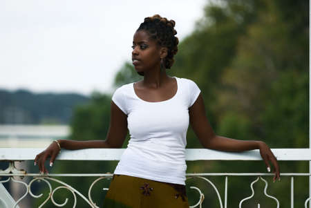 African American woman stands and relaxes on a bridge Stock Photo