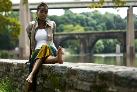 African American woman sits and relaxes by the river front Stock Photo