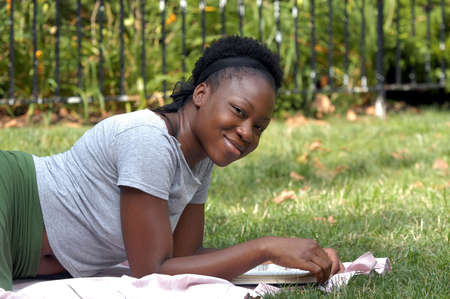 Young  afican american lady looks up from a book and smiles. Stock Photo