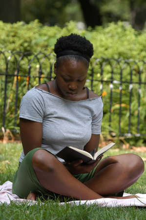 Young african american woman sits and reads in the park