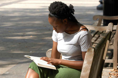 Young african american woman reads on a park bench.
