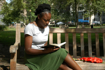 Young woman sits on a bench in a park and reads.