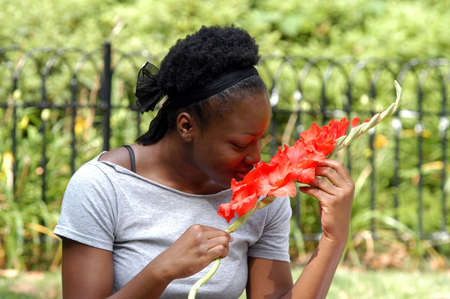 Young african american woman smells flowers, while sitting in the park Stock Photo