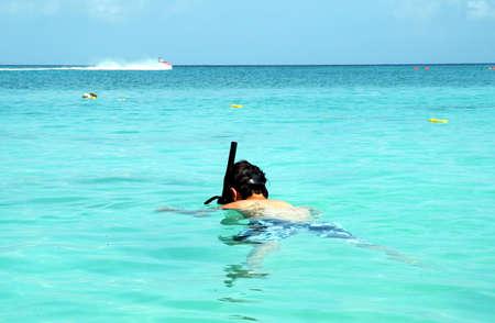 A boy snorkeling in clear water