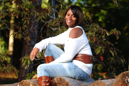 African-American woman sitting on log smiling Stock Photo