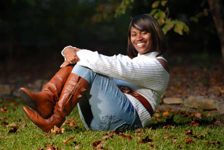 African -American woman sitting on grass smiling Stock Photo