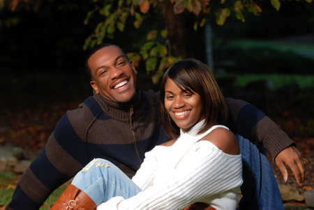 African-American Couple smiling sitting in the grass