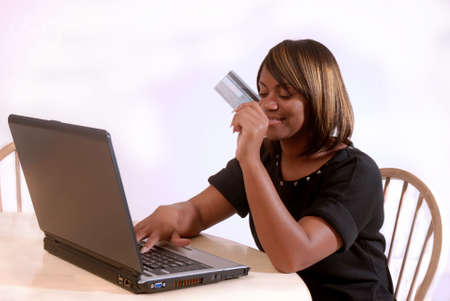 pay bills: African-American woman online shopping on the computer