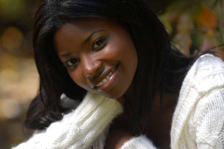 A close-up of an African-American woman sitting outside
