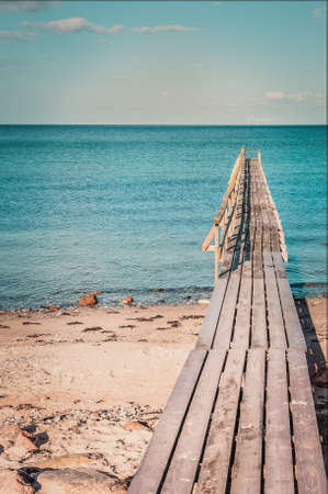 Wooden bridge on a tropical island, transparent sea and blue sky, advertising for tourism