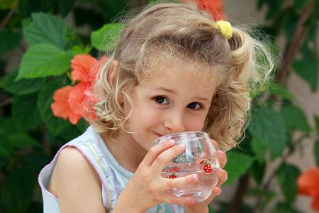 Smailing blond  girl with a glass of water