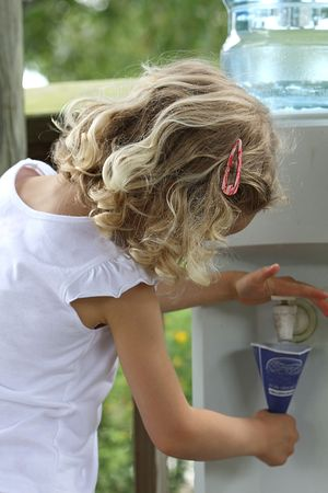 Little girl pouring water in paper cup photo