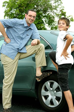 Casual portrait of man and kid by the car Imagens