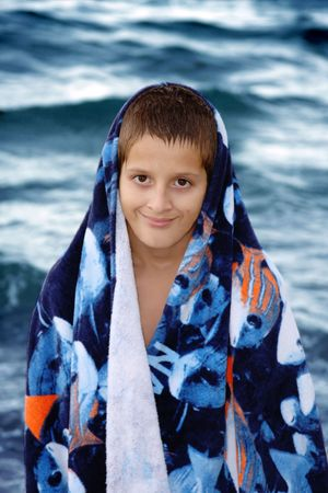 Boy wrapped in towel, relaxing after swiming  photo