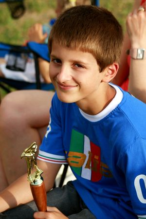 Smiling boy with baseball trophy